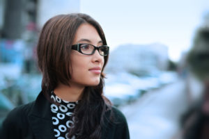 Person in glasses against city backdrop