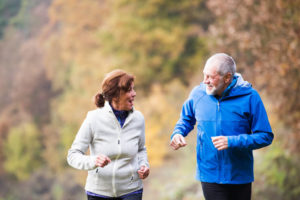 Active older couple running in the fall