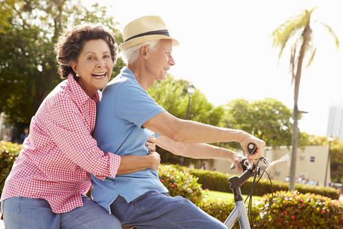 Older couple riding on bike.
