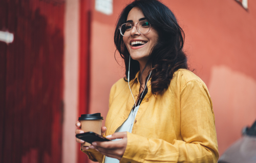 Smiling Young Woman Using Phone and Drinking Coffee