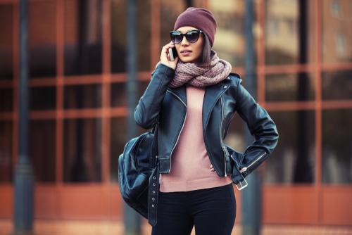 Fashionable young woman in leather jacket and scarf talking on phone
