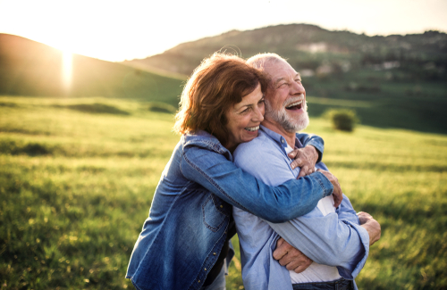 Middle-Aged couple laughing and embracing in grassy field