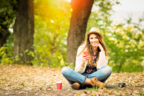 Stylish young woman sitting in the woods using cell phone