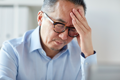 Middle-aged man with glasses looking tired and holding head