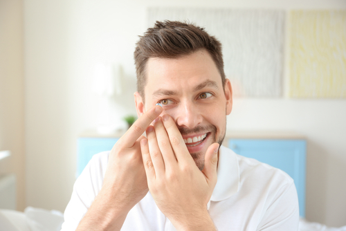 Smiling young man inserting contact lens