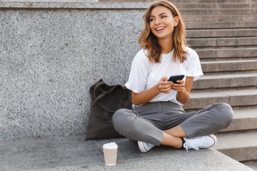 Smiling young woman sitting on steps and using cell phone