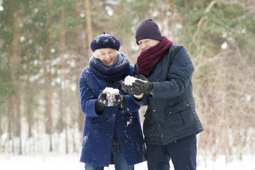 Older couple in woods playing with snow balls