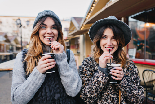 Two young women smiling and sipping drinks outside