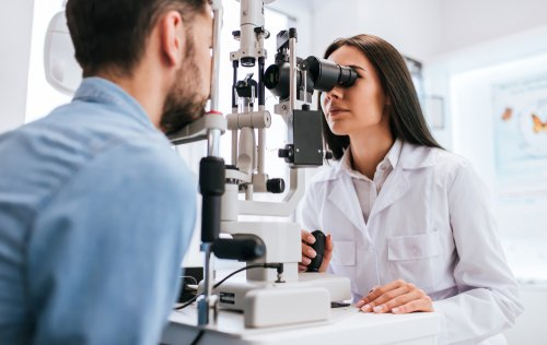 Female eye doctor performing eye exam on male patient