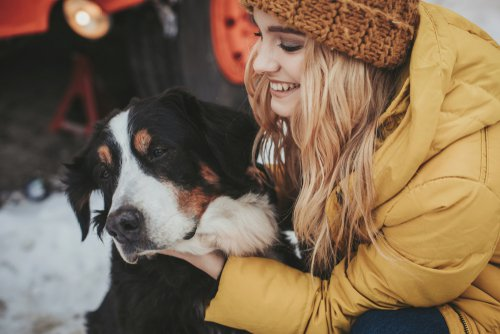 Smiling young woman in winter clothes petting a large dog
