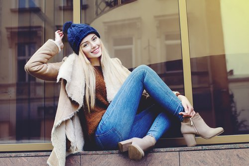 Smiling young woman sitting on ledge in front of window