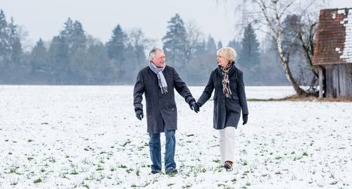 Happy older couple holding hands and walking through a snowy field