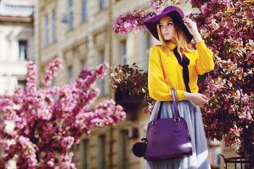 Young woman standing in front of purple trees