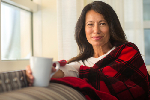 Woman with cup of coffee wearing blanket