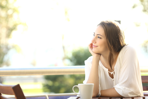 woman smiling while having coffee