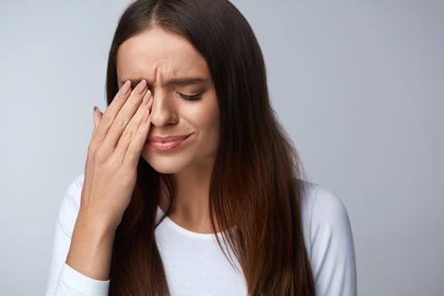 woman wiping eyes from dry eye symptoms
