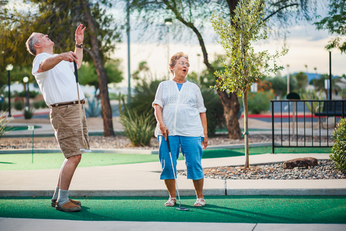 older couple playing mini golf