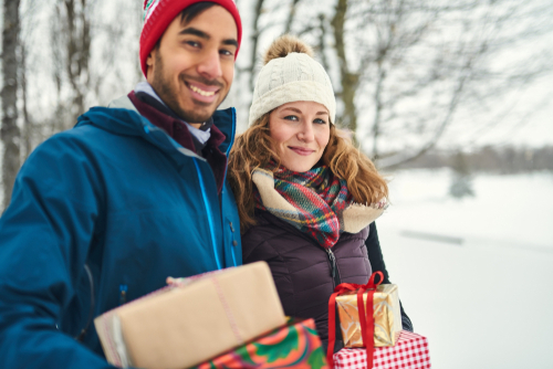 A couple smiling while holding present in front of a snowy background