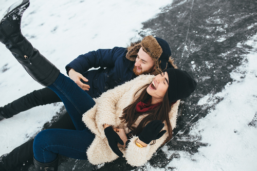 man and woman smiling while laying in the snow