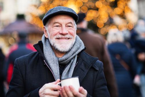 An elderly man smiling and holding a mug