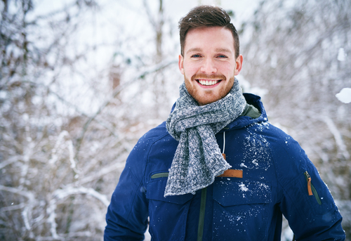 man in winter clothing standing outside while it snows