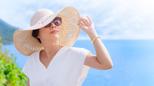 woman in white hat and sunglasses standing in front of the ocean
