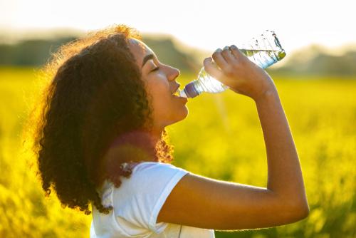 woman drinking from water bottle