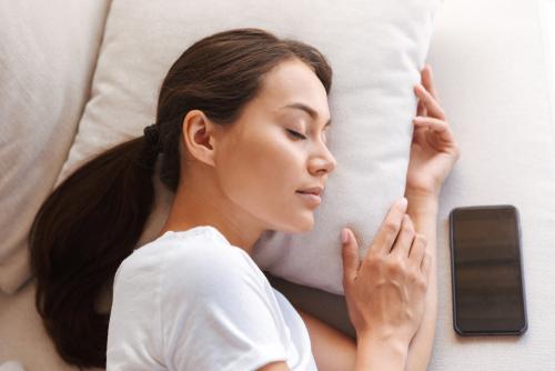 Woman sleeping next to phone